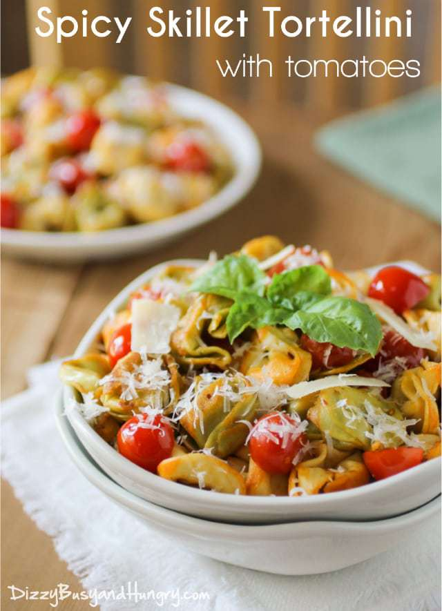 Side view of spicy skillet tortellini in a white bowl garnished with herbs.