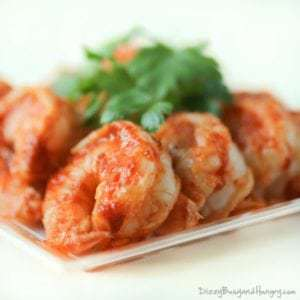 Close up shot of sweet and spicy grilled shrimp garnished with herbs on a white plate