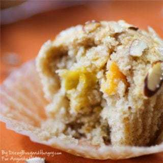 Side view of mango muffin in the liner on an orange cloth.