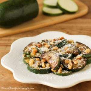 Side view of sautéed zucchini with walnuts on a white plate with a half sliced zucchini in the background.