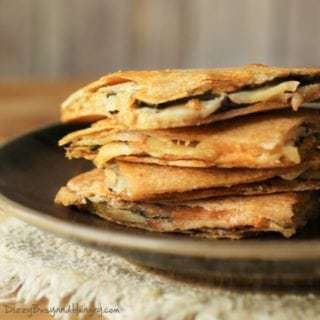 Close up shot of cheesy eggplant apple quesadillas stacked on a brown plate.