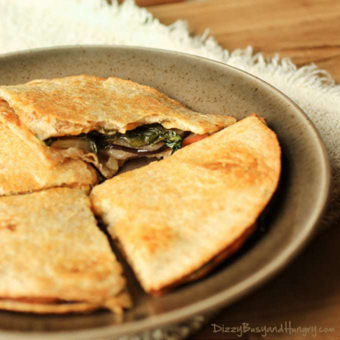 Close up shot of four cheesy eggplant apple quesadillas on a brown plate.