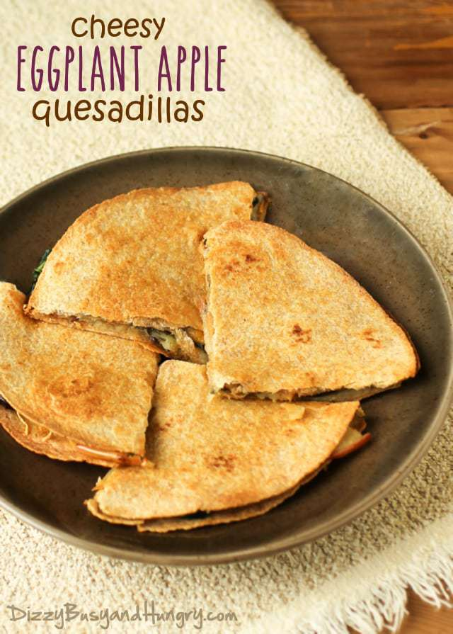 Overhead shot of four cheesy eggplant apple quesadillas on a brown plate.