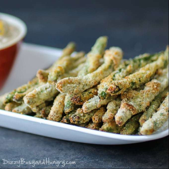 A plate filled with crispy green bean fries. A small red bowl with dip is on the side