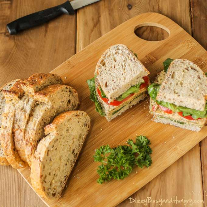 Side view of eggplant Milanese torta cut in half on a wooden cutting board with more sliced bread on the side.