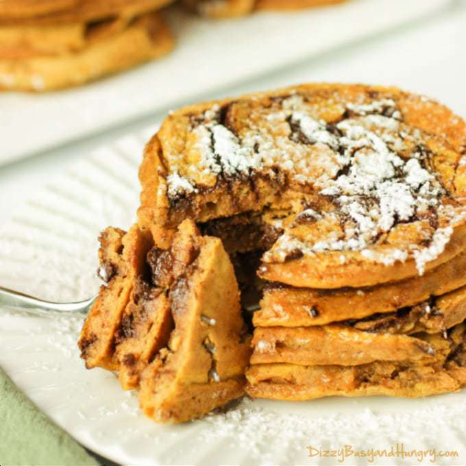 Side view of a fork taking a slice of pumpkin chocolate swirl pancakes stacked on a white plate.