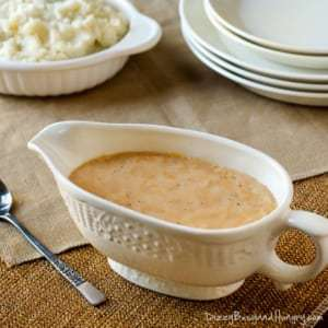 Side view of homemade gravy in a white gravy boat with a white bowl of mashed potatoes and a wooden spoon in the background.