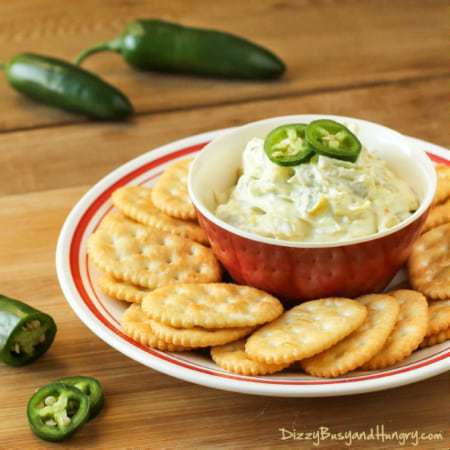 Side view of jalapeño artichoke dip surrounded by crackers on a red and white dish with jalapeños in the background.