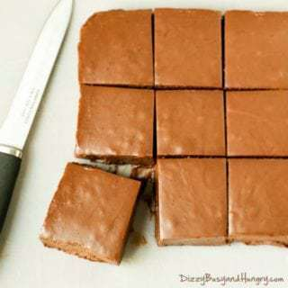 Overhead shot of microwave pumpkin fudge cut into squares with a knife on the side.