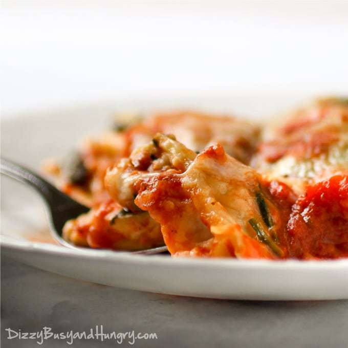 Close up shot of ravioli spinach bake on a white bowl with a fork.