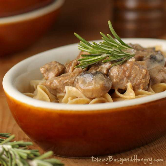 Side shot of crockpot beef stroganoff in an orange oval bowl on a wooden surface.