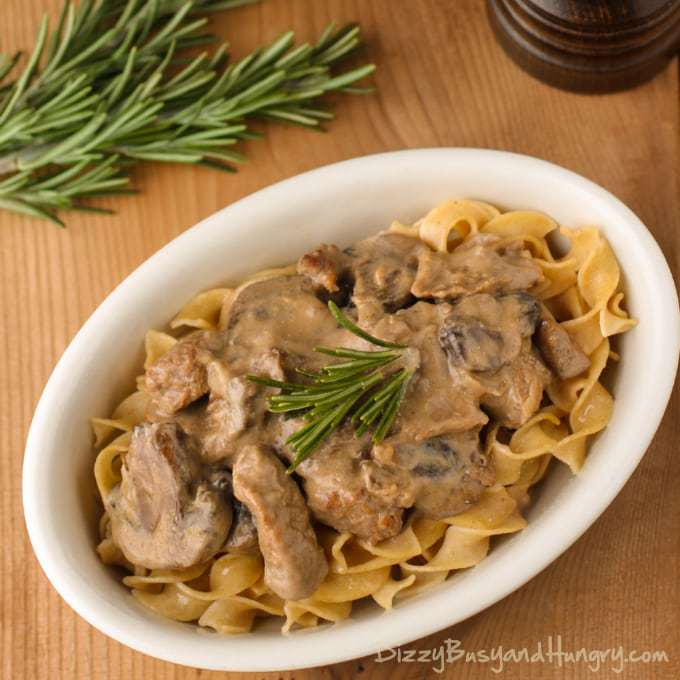 Overhead shot of crockpot beef stroganoff in a white oval bowl on a wooden table with herbs in the background.