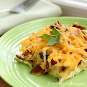 Close up shot of bacon breakfast casserole garnished with herbs on a green plate with a white cloth and a fork on the side.