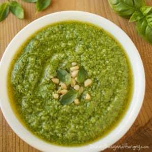Overhead shot of broccoli pesto in a white bowl on a wooden surface with herbs sprinkled around.