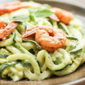 Close up shot of creamy avocado noodles with chipotle lime shrimp on a wooden plate.
