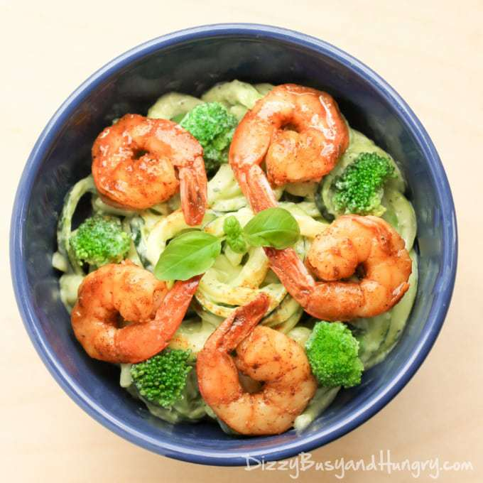 Close up shot of creamy avocado noodles with chipotle lime shrimp in a blue bowl.