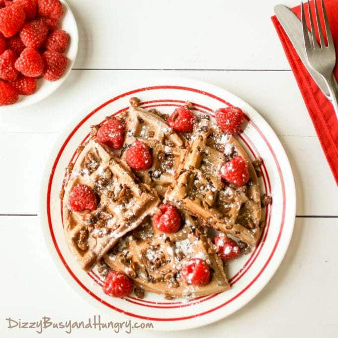 Overhead shot of chocolate crunch raspberry waffles sprinkled with powdered sugar and raspberries on a white plate with a bowl of raspberries in the background.