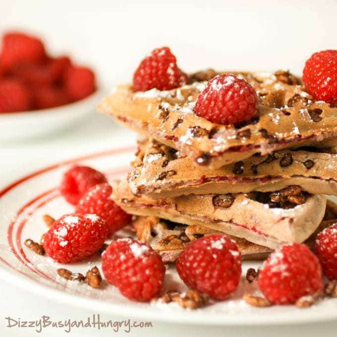 Close up shot of chocolate crunch raspberry waffles sprinkled with powdered sugar and raspberries on a white plate.