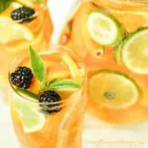 Close up shot of sparkling citrus sangria in a clear glass with a large pitcher of it in the background.