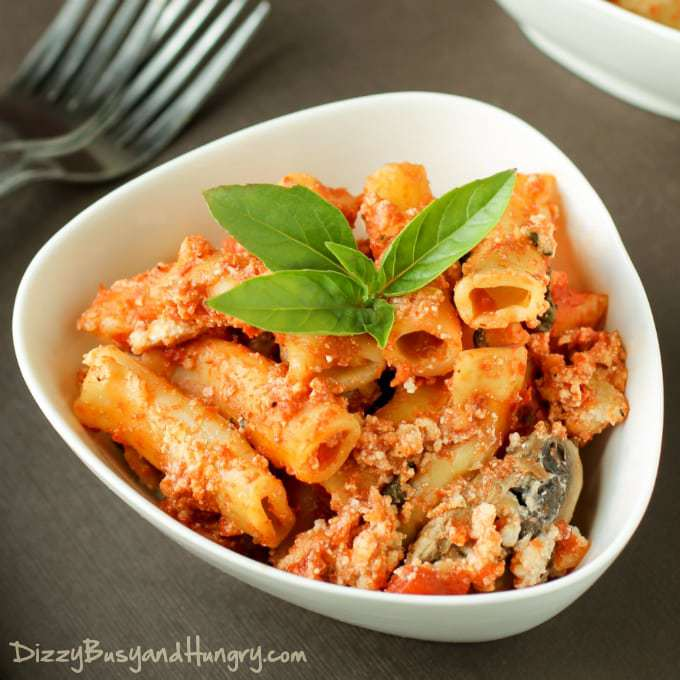 Side shot of slow cooker baked ziti garnished with herbs in white bowl with forks in the background.