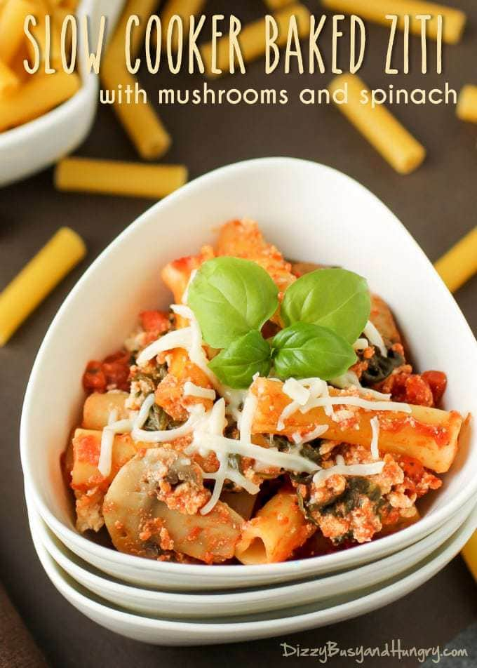 Close up view of slow cooker baked ziti garnished with herbs in a white bowl.