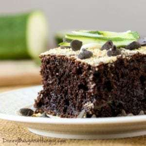 Close up shot of chocolate zucchini cake on a white plate with sliced zucchini in the background.