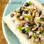 Close up shot of black bean ranch tuna salad in a bun on a blue plate.