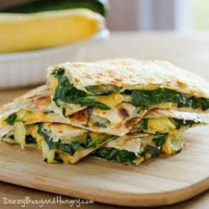 Side shot of cheesy zucchini spinach quesadillas stacked on a wooden cutting board.