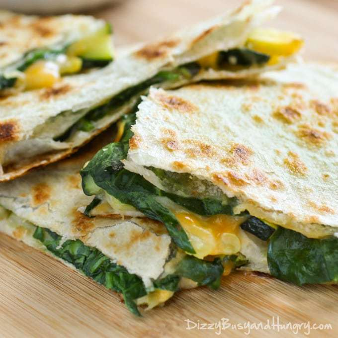Close up shot of cheesy zucchini spinach quesadillas layered on a wooden cutting board.