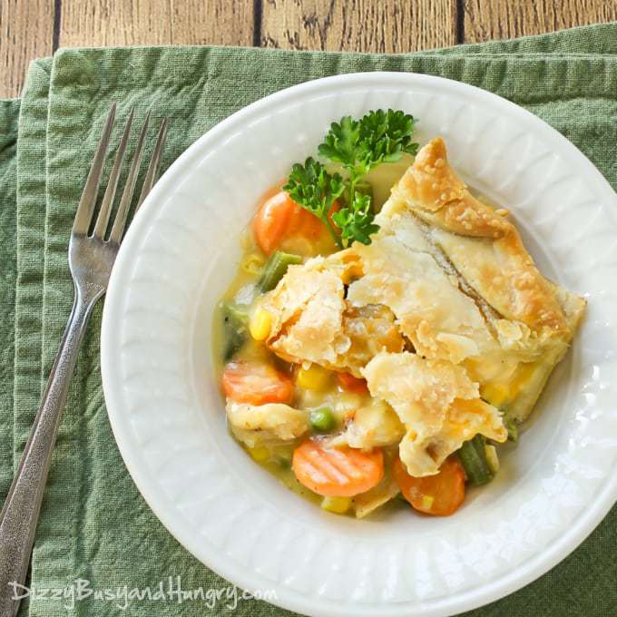 Overhead view of a slice of super easy chicken pot pie with the vegetables falling out of it and a parsley leaf for garnish