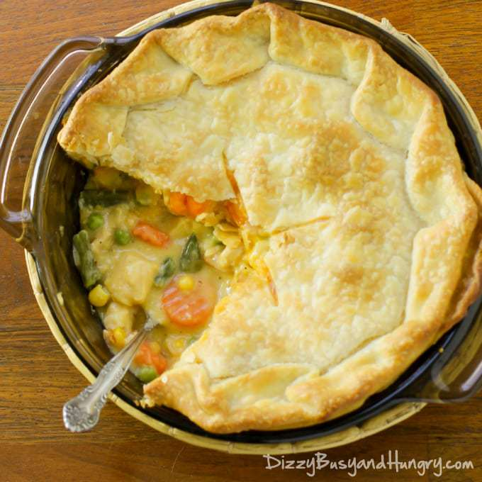 Overhead view of super easy chicken pot pie with part of the crust removed to show the inside of the pie.  Vegetables, chicken and gravy are visible inside.  A spoon is placed inside the pie
