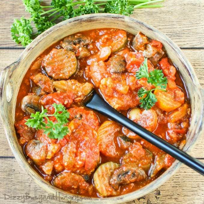 Overhead shot of slow cooker chicken cacciatore in a wooden bowl with a black spoon and herbs in the background.
