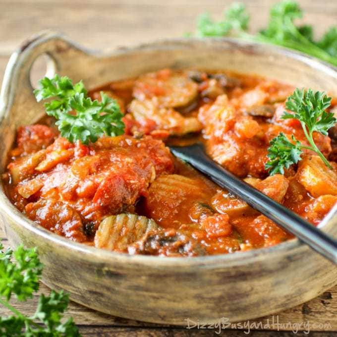 Close up shot of slow cooker chicken cacciatore in a wooden bowl with a black spoon and herbs in the background.