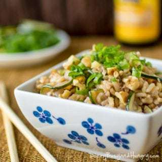 Side view of zucchini walnut fried rice in a white and blue bowl with chopsticks on the side.