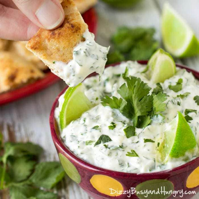 Close up shot of a chip being dipped into cilantro lime dip with sliced limes and cilantro in the background.