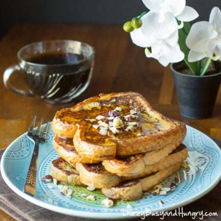 Side shot of Kahlua and cream French toast stacked on a blue plate with syrup and a fork on the side with a cup of coffee in the background.