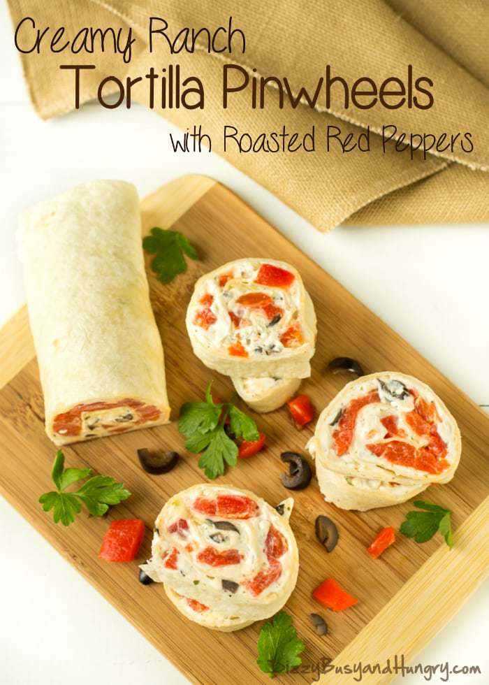 Overhead view of creamy ranch tortilla pinwheels on a wooden cutting board garnished with herbs, tomatoes, and olives.