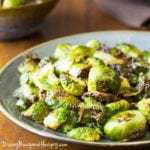 Close up shot of roasted Brussels sprouts on a grey plate on a wooden table.