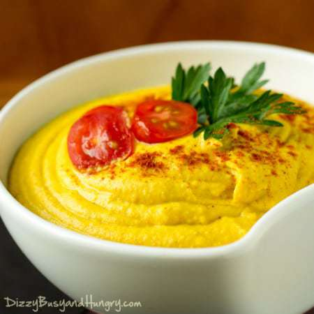 Close up shot of turmeric hummus in a white bowl garnished with tomatoes and herbs.