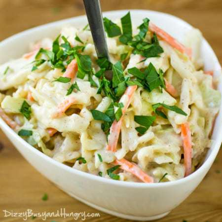 Close up shot of chipotle lime Cole slaw garnished with herbs in a white bowl on a wooden table.
