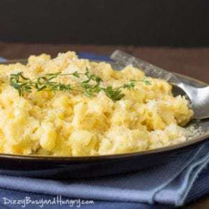 Side view of cauliflower Mac and cheese garnished with herbs on a grey plate with a spoon on the side on a blue cloth.