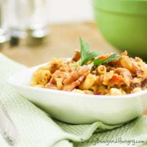 Side view of bacon and pumpkin pasta garnished with herbs in a white bowl on a green cloth.
