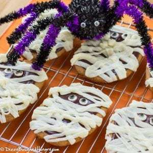 Close up shot of peanut butter mummy cookies on a drying rack with a fake spider on top.
