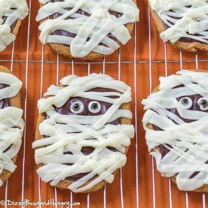Close up shot of peanut butter mummy cookies on a drying rack with an orange background.