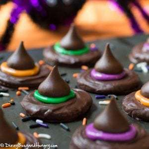 Close up shot of witch hat cookies lined on a black surface with halloween themed sprinkles.