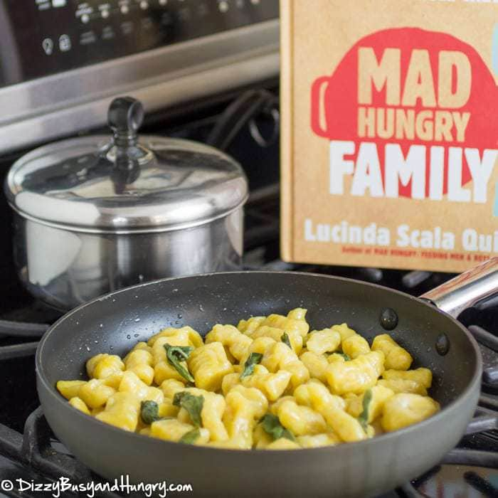 "Side view of a pan with squash gnocchi on the stove with another pan and the book ""Mad Hungry Family\"" in the background."