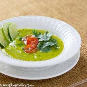 Side shot of zucchini curry lime soup garnished with herbs tomatoes and sliced lime in a white bowl on a white plate.