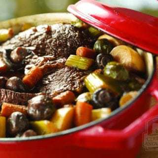 Close up shot of braised pot roast with root vegetables in a red pot.