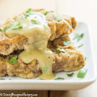 Up close view of 2 pieces of chicken fried steak on a white plate with a yellow gravy