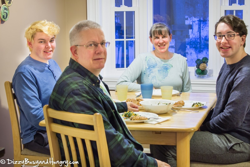 Side view of a family of four sitting at a table eating dinner.